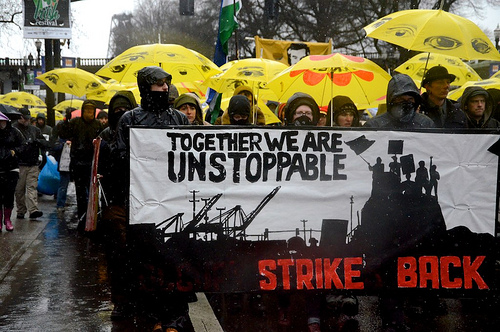 Protesters with sign: Together we are unstoppable.  Strike back.