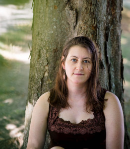 Photo of a white woman in a dark shirt in front of a tree