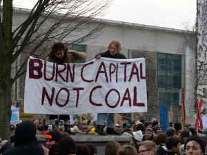 "students holding sign ""burn capital not coal"""