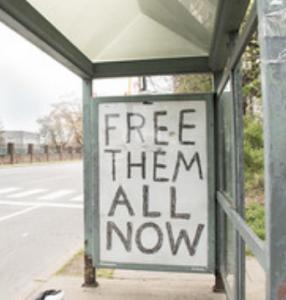 """graffitti saying """"Free Them All"""""""