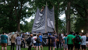 Activists surrounded by cops obscure the Silent Sam statue before it is torn down