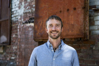Jason Rasor wearing a blue shirt and jewelry smiles while standing in front of a brick wall with rusted metal sections.